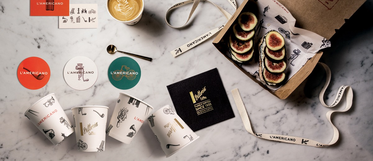 A collection of L'Americano Vittoria Coffee cups and a box of figs lying open on a marble bench