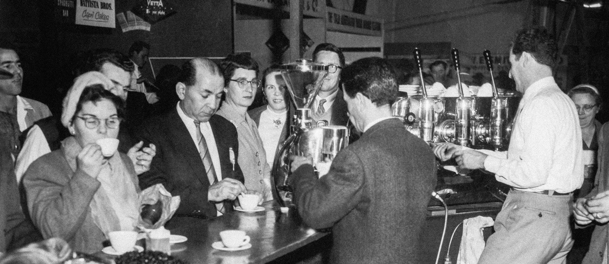 People gather at a standing cafe in 1950s Italy ordering and drinking espressos