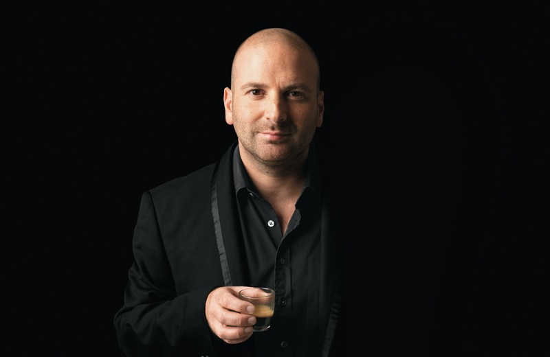 George Calombaris (chef) standing wearing a black jacket with a black shirt against a black wall