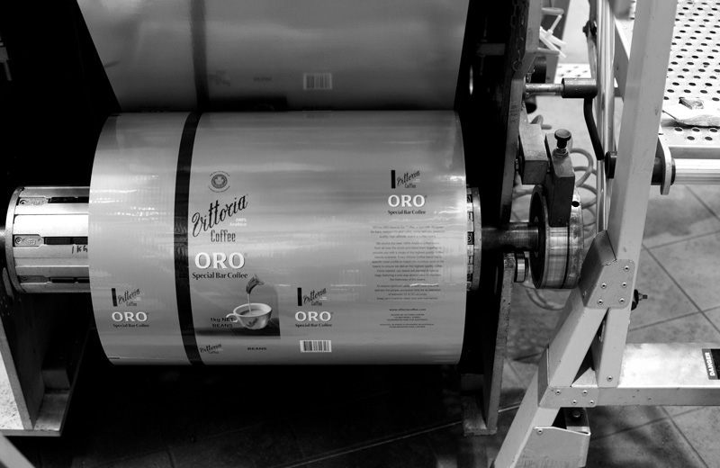 A label printing machine with a roll of print for Vittoria Coffee's Oro variety