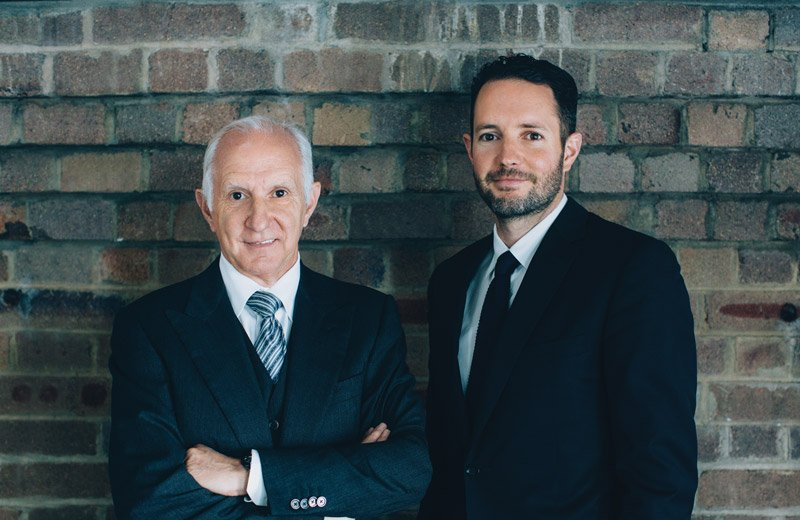 Vittoria Coffee CEO, Les Shirato and son MD, Rolando Shirato standing in front of an exposed brick wall