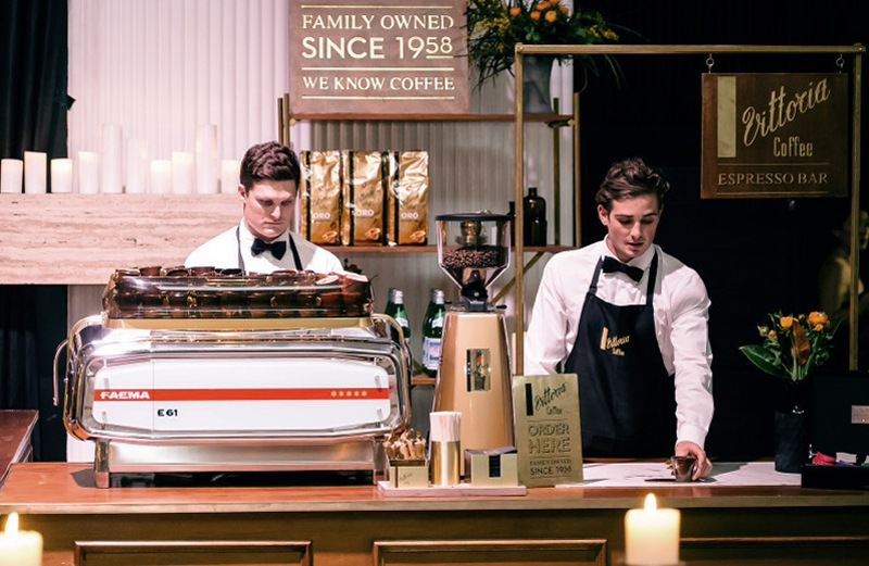 Two baristas dressed immaculately in crisp white shirts and black Vittoria Coffee aprons serving Vittoria Coffee at a pop-up store