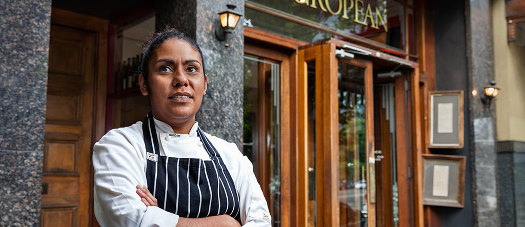 Indigenous chef stands with arms crossed