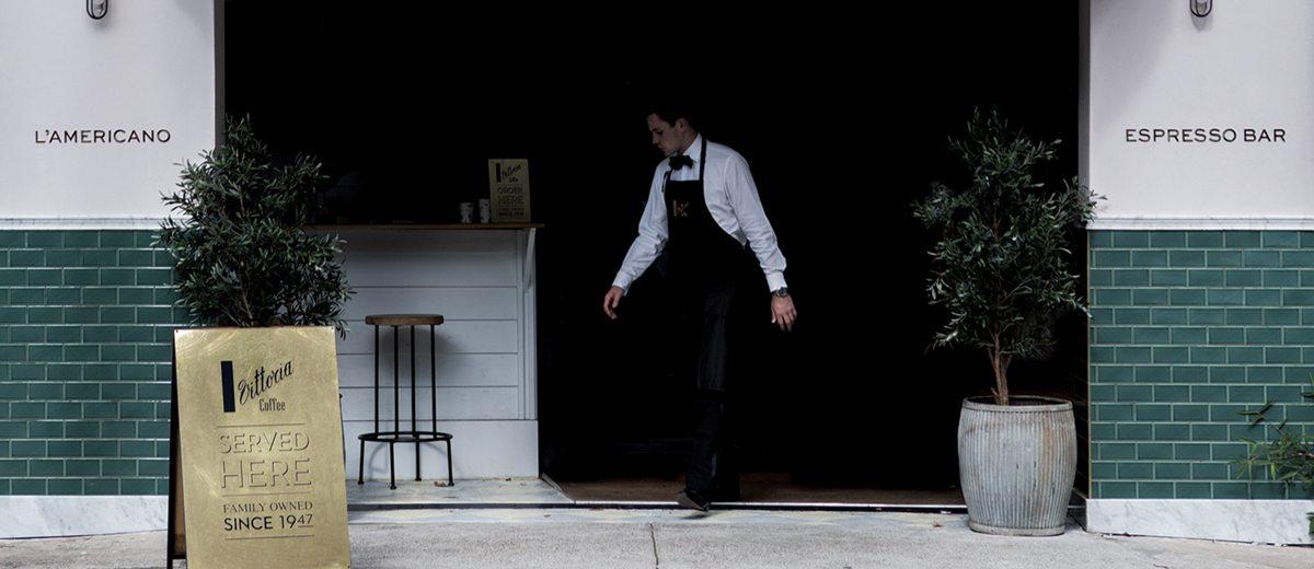 A barista walking out of L'Americano Espresso cafe in Alexandria, Sydney