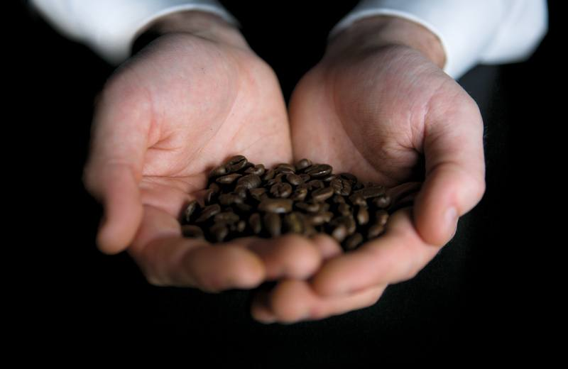 Two cupped hands holding a handful of Vittoria Coffee beans