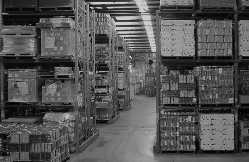 Numerous packages of Vittoria Coffee stacked on shelves in a warehouse