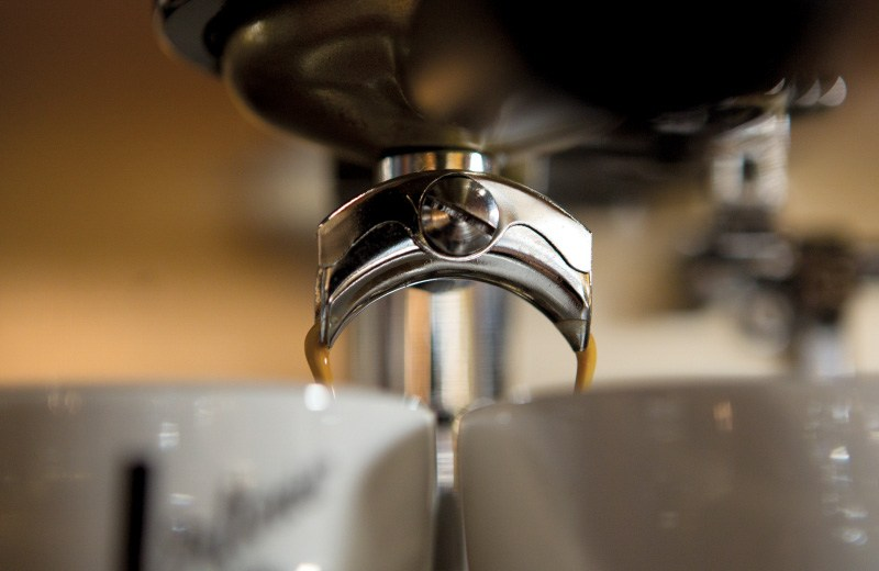 A close up of coffee pouring from a machine into two coffee cups