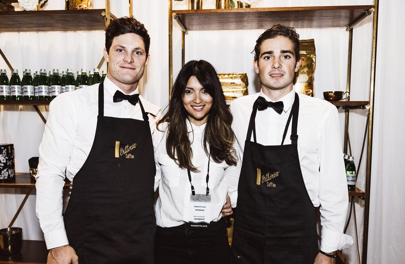 3 young Vittoria Coffee employees working at an event standing with arms around each others waists