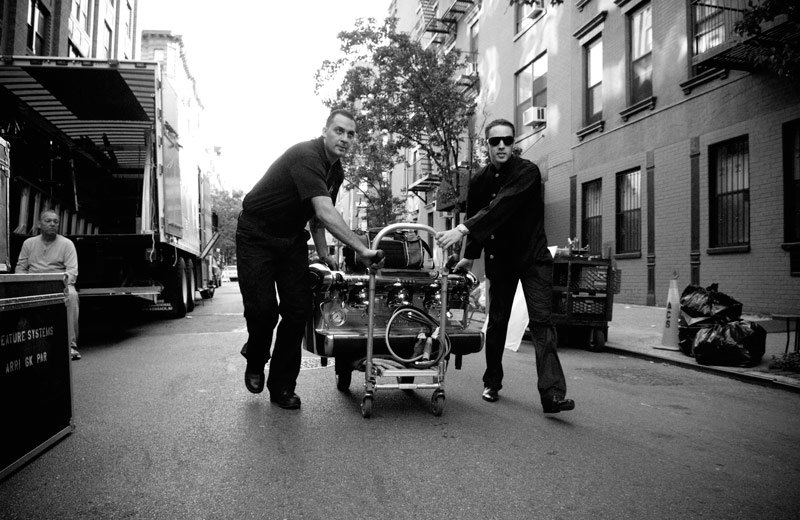 Two men wheeling a coffee machine down the street on a trolley