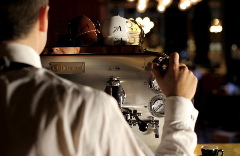 Looking over the shoulder of a barista making a Vittoria Coffee coffee