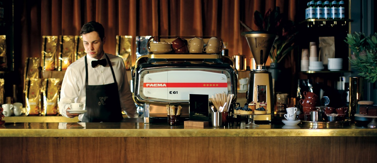 A barista dressed immaculately in crisp white shirt and black Vittoria Coffee apron serving Vittoria Coffee at a pop-up store
