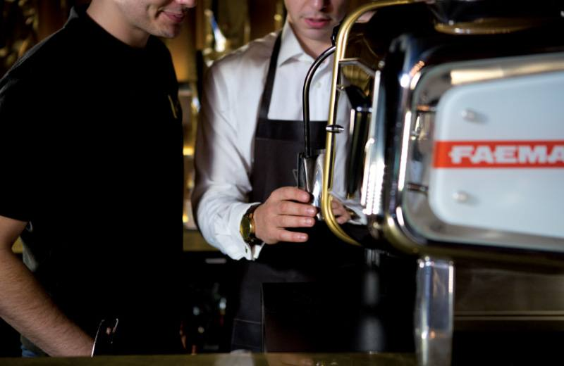 An experienced Vittoria Coffee barista trains a newcomer in the art of making coffee