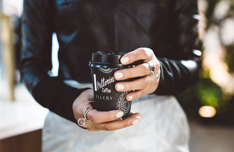 A woman holding an Ellery designed Vittoria Coffee cup