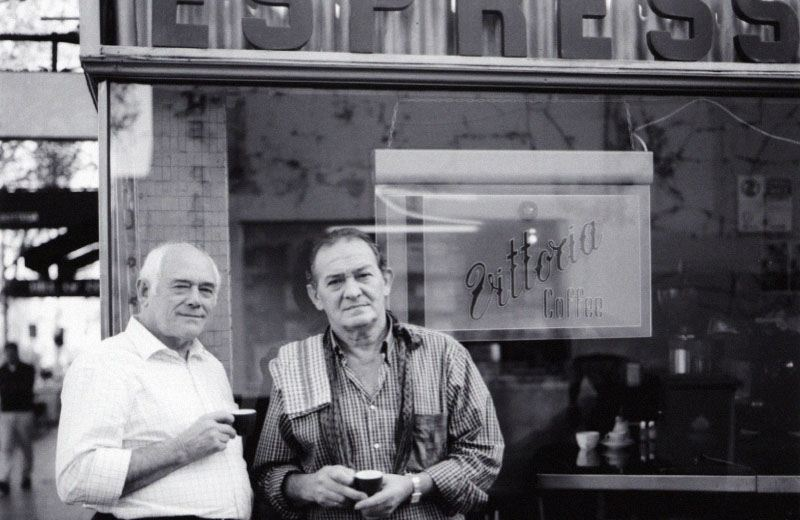 Two older Italian men standing out front of a cafe, with a hanging Vittoria Coffee sign in the window