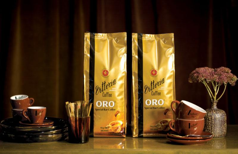 Two gold 1kg package of Vittoria Coffee Oro coffee beans flanked by a stack of cups and saucers
