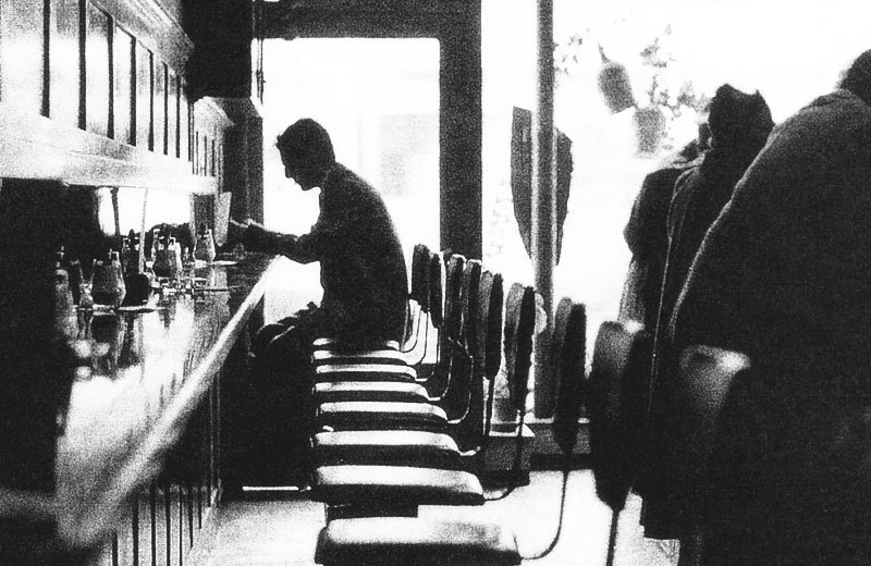 A grainy black and white image of a man sitting at a coffee bar in Italy in the 1950's
