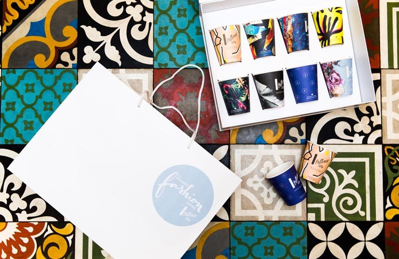 A decorative mosiac of coloured tiles with a box of Vittoria Coffee 'Fashion Series' coffee cups opened on top