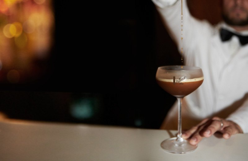 A bartender pouring the final drops of a Vittoria Coffee espresso martini from high above the Vittoria Coffee labelled glass