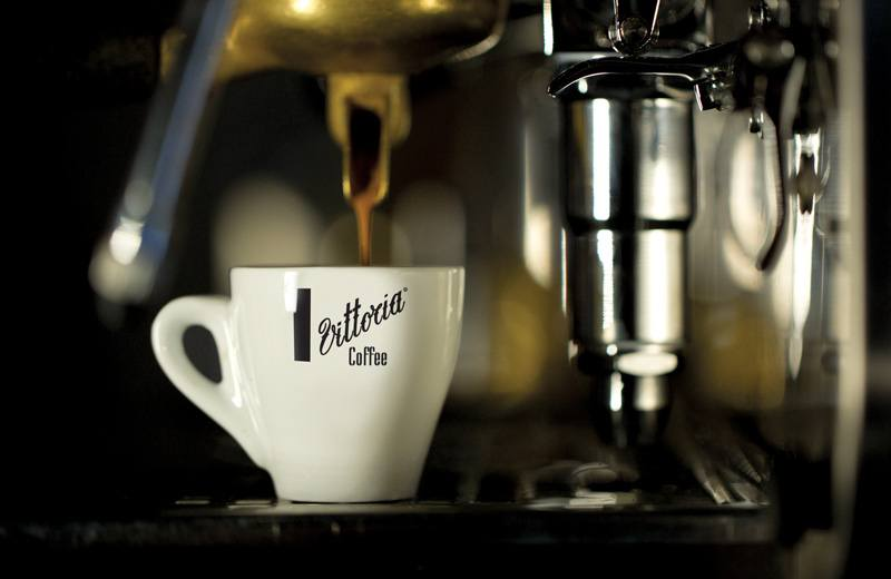A close up of a white Vittoria Coffee cup with some freshly ground coffee beans being made into coffee